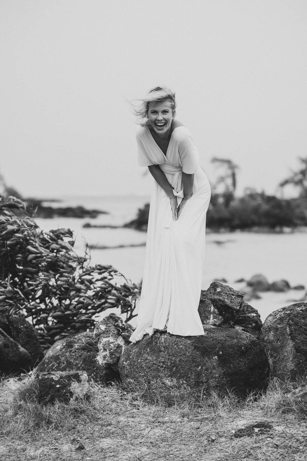 Copy of Sita Kelly | Mauritius Honeymoon Photographer | woman in white dress standing on a rock and laughing