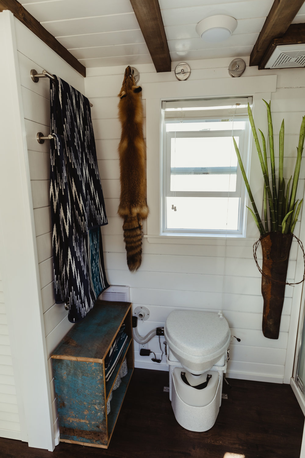 In a tiny house there is limited privacy. It's important that ALL the spaces are functional and beautiful. The towels and distressed shelves are practical and on theme with the rest of the house. The fox fur and old scabbard repurposed as a hanging vase add a touch of Wyoming whimsy.