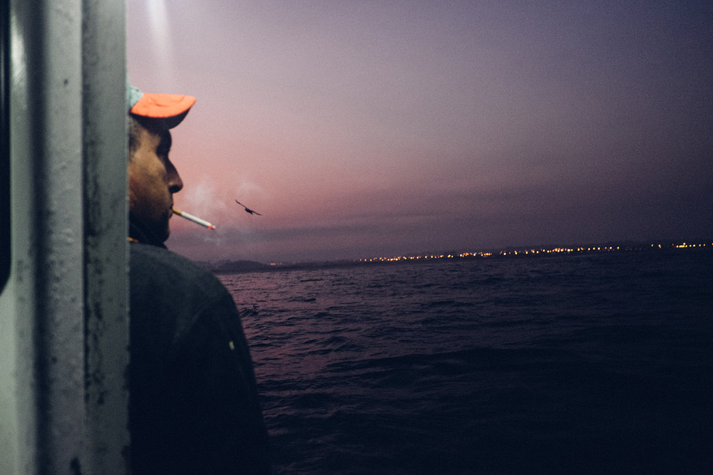 A fisherman at dawn on his boat; Because of my grandfather's life history with the sea I felt I needed to experience the sea. Consequently, for some nights, I embarked on a boat with local fishermen along Vila do Conde's coast. August 2016.