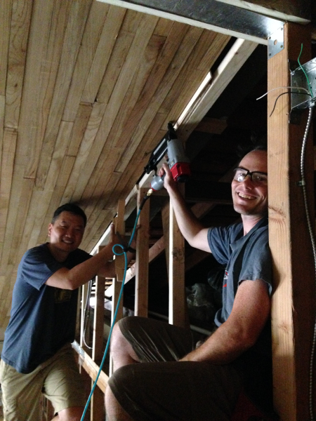 Sang and Chris install the final piece of paneling.