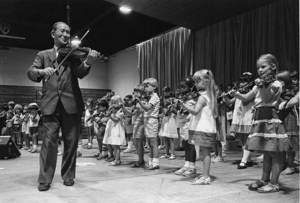 Shinichi Suzuki, the inventor of the Suzuki method of music education, playing the violin with students.