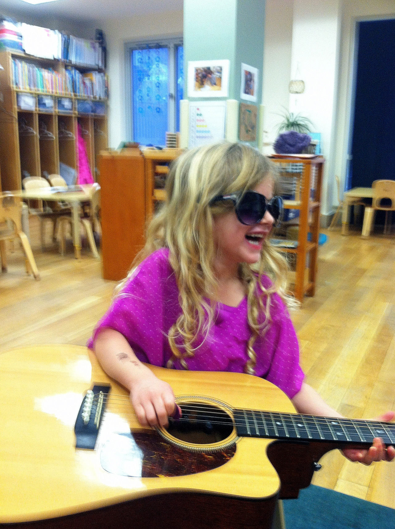 This girl is rockin' cool sunglasses in her guitar class! Rock on.