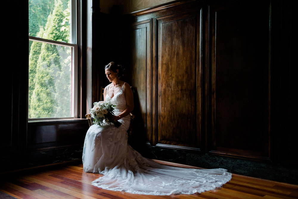 Bride looking at her bridal bouquet in a moody room at Lucile's Old Market in Omaha Nebraska