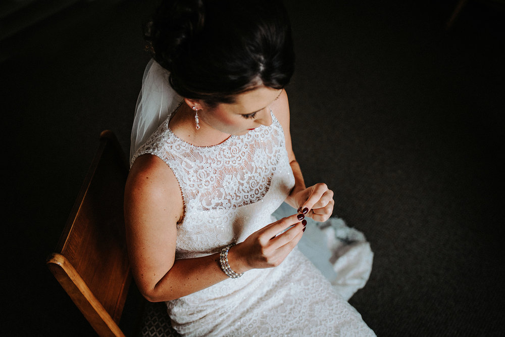 bride in window light looking at grandmother's ring