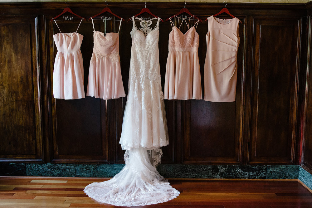 bridal gown and bridesmaids dresses hanging against dark wood wall at Lucile's Old Market