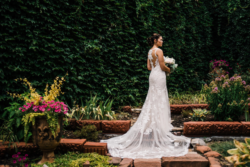 bride posing in front of ivy wall at lucile's old market in Omaha