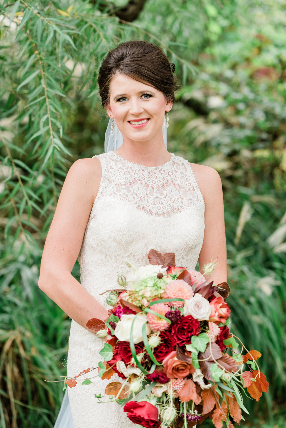 bride smiling with her florals before her fall wedding in reinbeck, ia