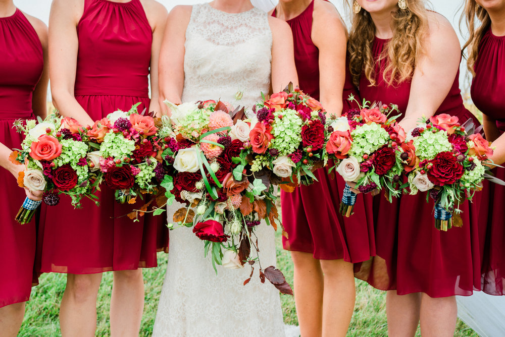 Red bridesmaids dresses with gorgeous fall florals at a reinbeck, IA wedding.