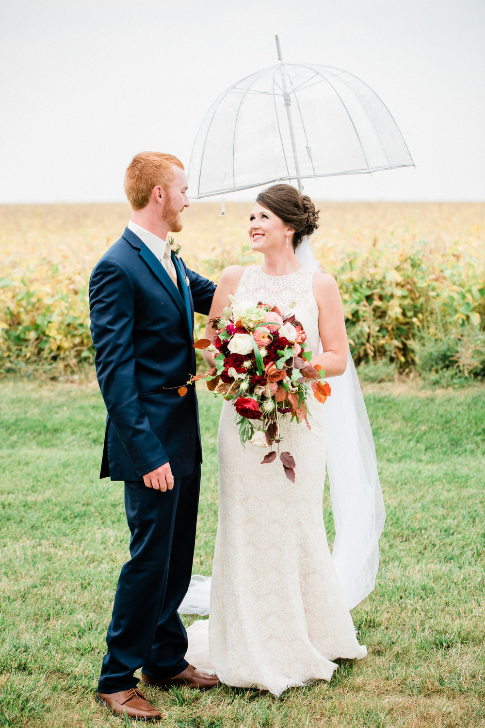 happy bride and groom with an umbrella on a rainy wedding day in reinbeck, ia.