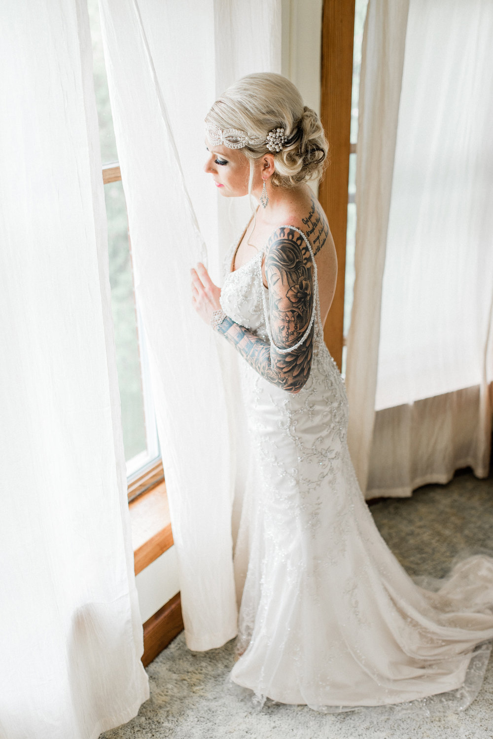 Tattooed bride looking out of a window on wedding day.