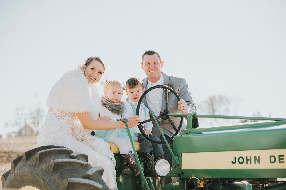 Bride and groom on a tractor with their flower girl and ring bearer at their farm wedding in Great Mills, IA