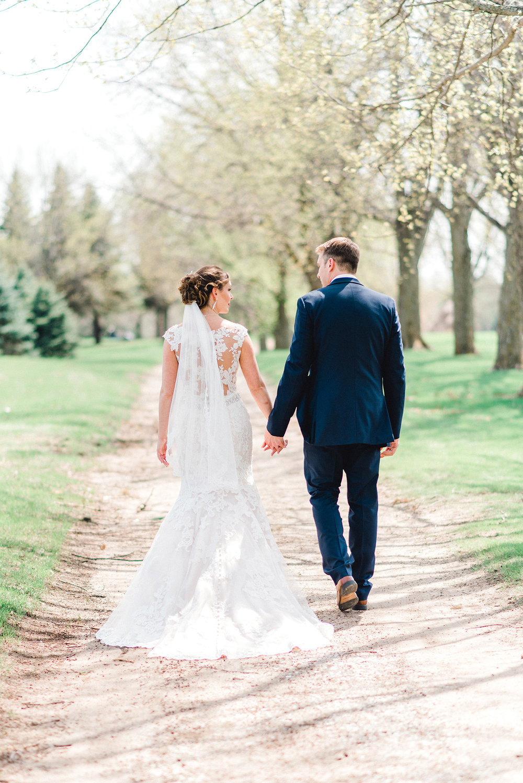 Bride and Groom Walking Omaha Wedding Photographer Nicole Corrine.jpg