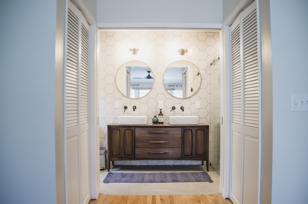 Master bathroom with refurbished credenza as vanity and his/hers closets with shuttered doors