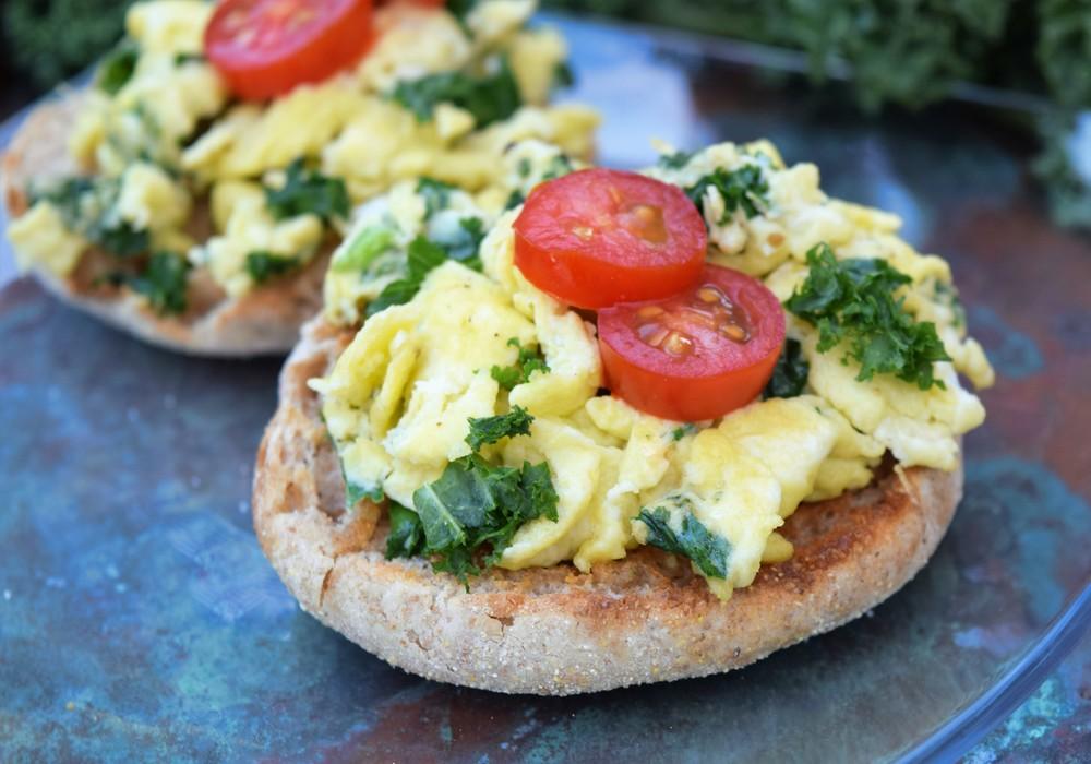 Un muffin anglais de blé entier avec un œuf brouillé et du chou vert frisé