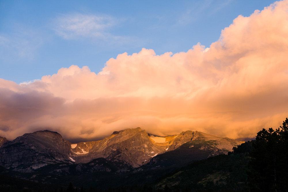 Lever de soleil sur les montagnes à Rocky Mountain National Park. Les nuages s'accrochent au sommet.