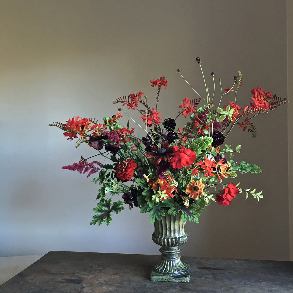 An arrangement of reds and greens—complementary colours—showing a range of reds: oranges, crimsons, scarlets, burgundies and plums. Plants include  Crocosmia  'Lucifer',  Pelargonium quercifolium  'Chocolate-Mint',  Scabiosa atropurpurea  'Black Knight', Geranium,  Astilbe ,  Molucella ,  Sanguisorba ,  Pittosporum  'James Stirling',  Helenium , Echibeckia, sweet peas and Zinnia 'State Fair'.