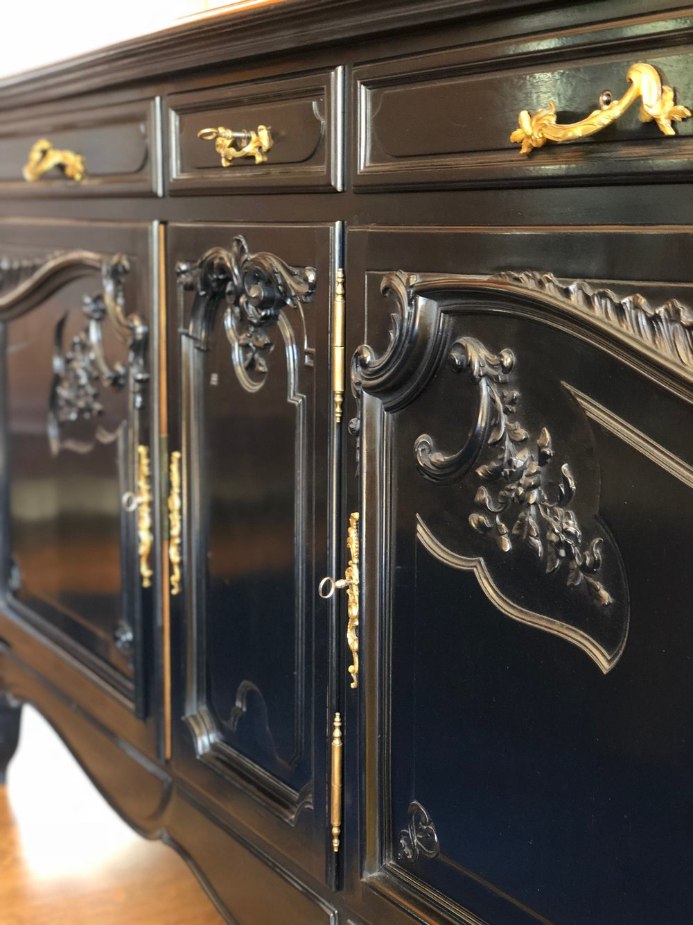 Revitaliste refinished the Antique French Sideboard in an ebonized wood finish and polished the ornate brass drawer pulls and hinges.