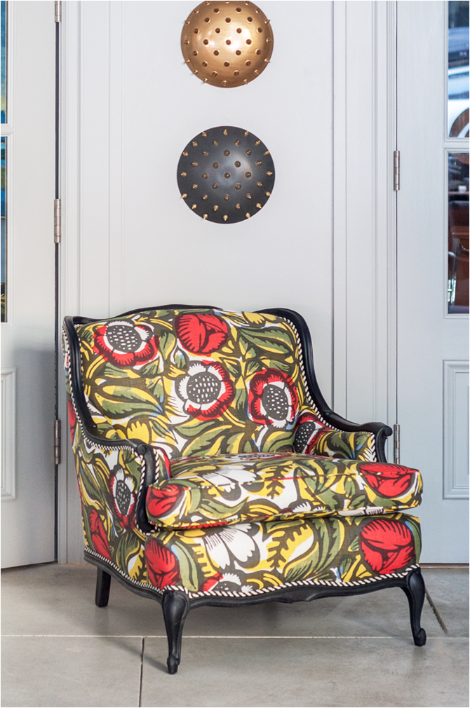"Revitaliste reupholstered this Vintage Bergère Chair in Christopher Farr Cloth ""La Floret"" in Berry and refinished the wood frame in a matte black wood stain."