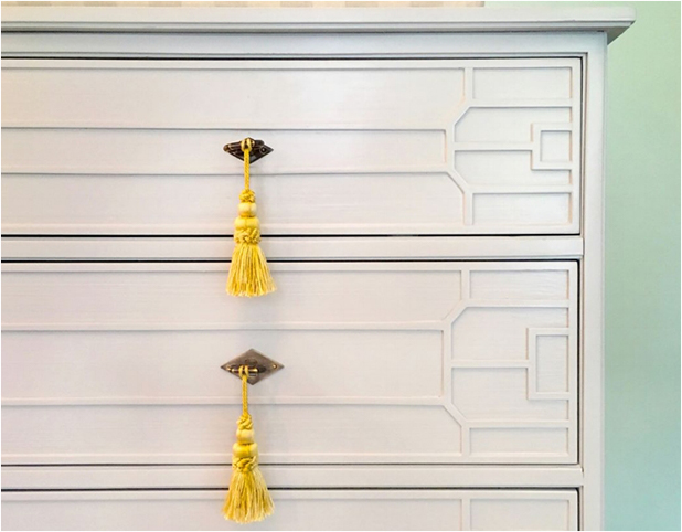 Revitaliste refinished the dresser in a pale grey custom color lacquer and replaced the hardware with brass escutcheons with yellow tassels.
