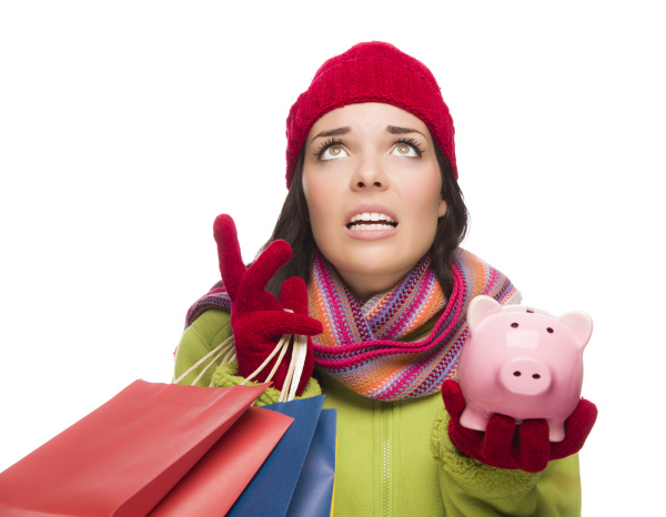 Stressed Mixed Race Woman Wearing Winter Clothing Looking Up Holding Shopping Bags and Piggybank Isolated on White Background.
