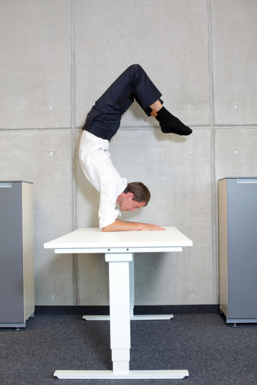 flexible business man in scorpion asana on desk in his office