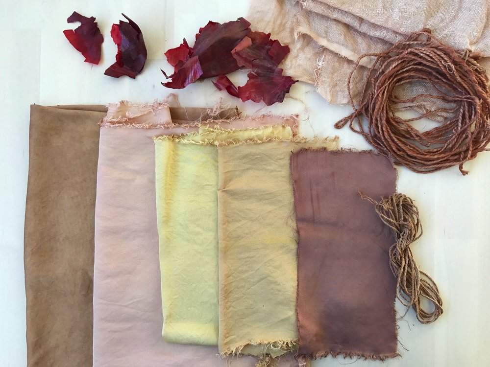 The range of shades from red onion skins on bamboo fabric. Also show: tencel yarn and unmordanted linen fabric above, and hemp cord on the right.