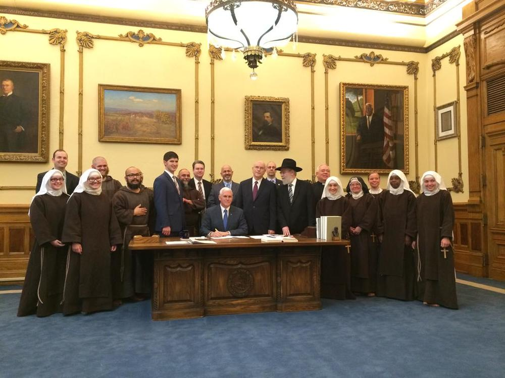 Governor Mike Pence of Indiana signs the disastrous state RFRA into law.