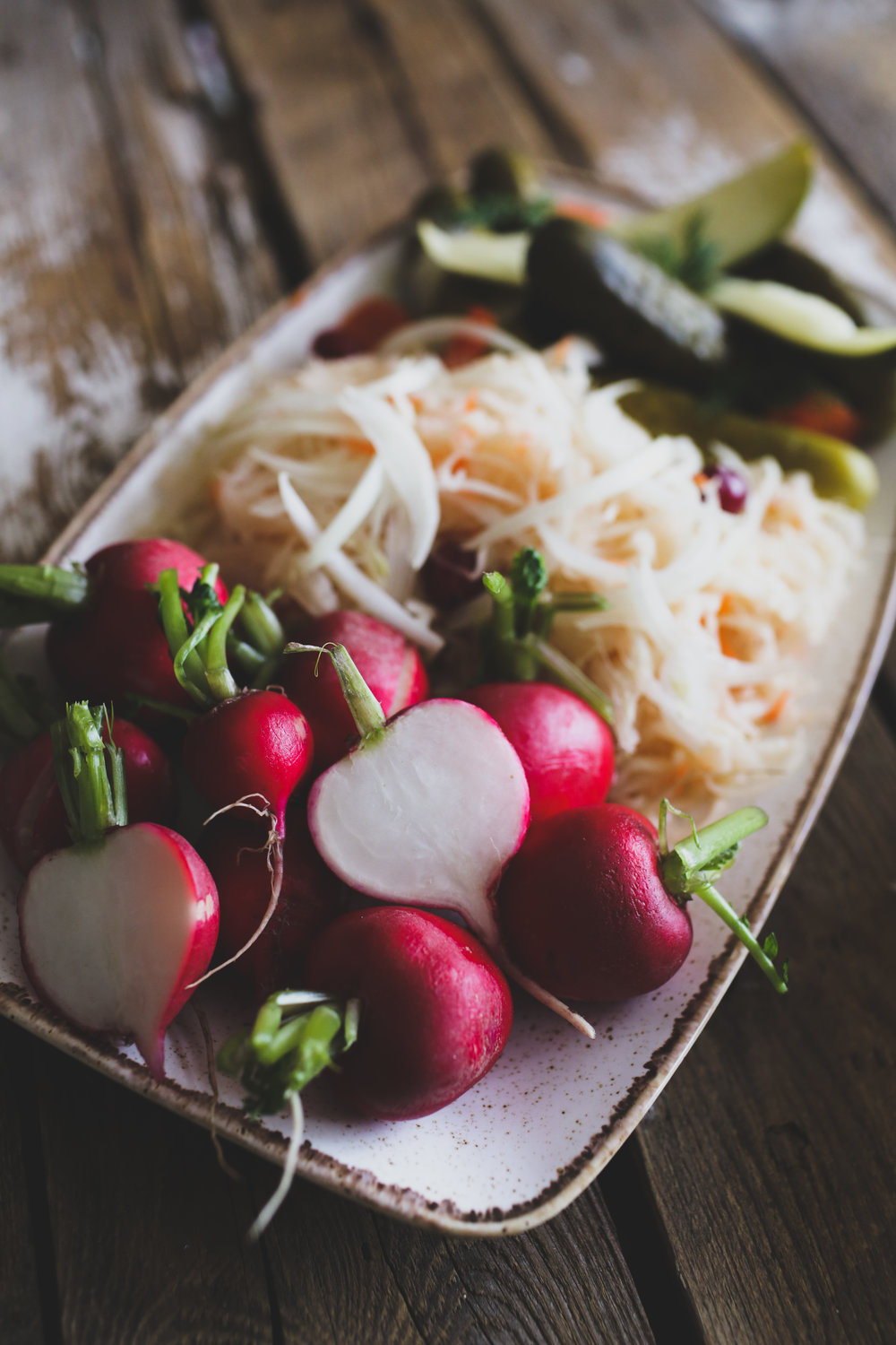 Bright pink orbs of radishes, alongside Russian-style sauerkraut, and pickles.
