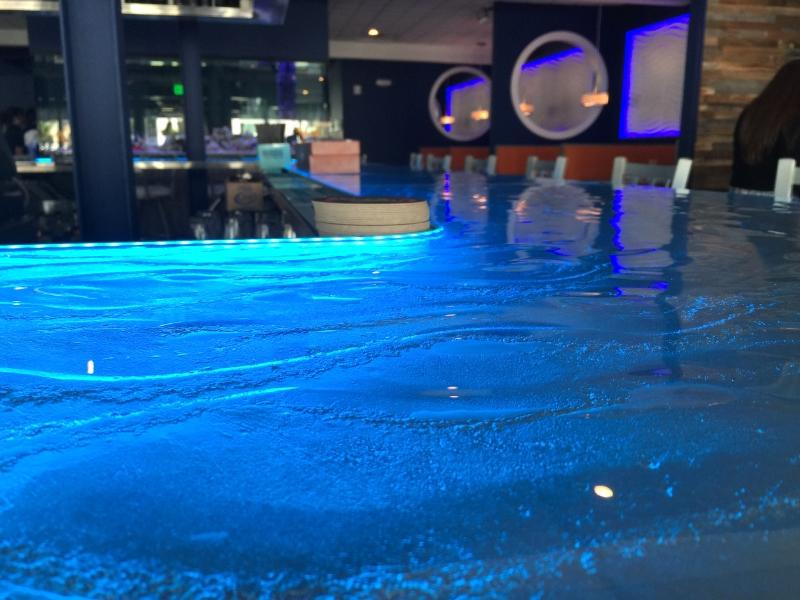 Custom LED lit poured glass bar top by the restaurant designer