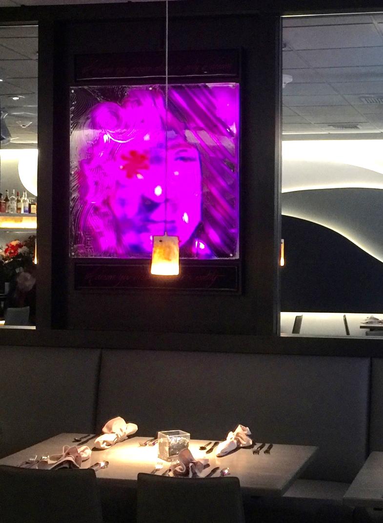 """After"", the restaurant designer added encased mirrors and LED artwork above banquette"