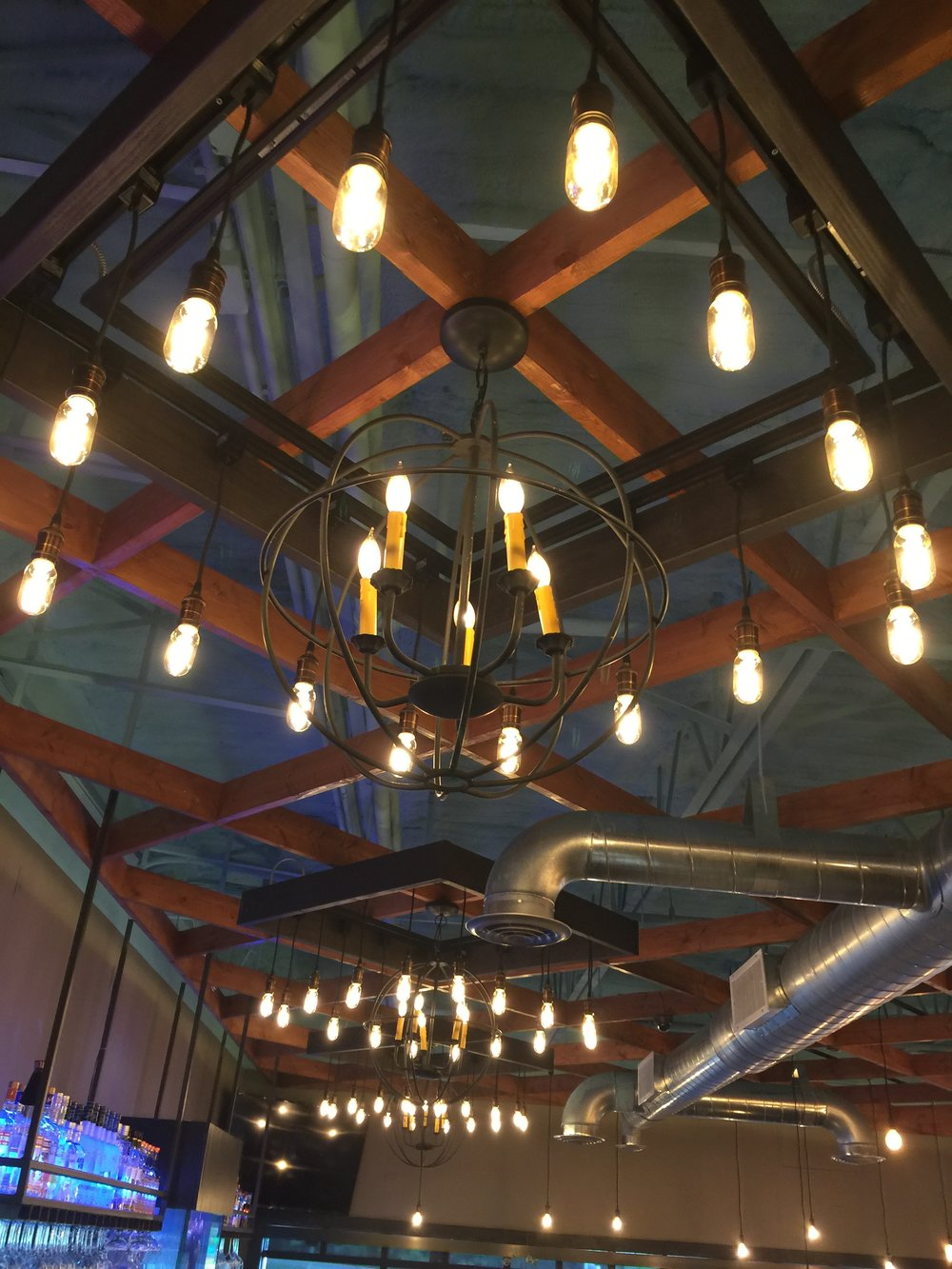 3 Custom Fabricated Filament Bulb Chandeliers over Bar