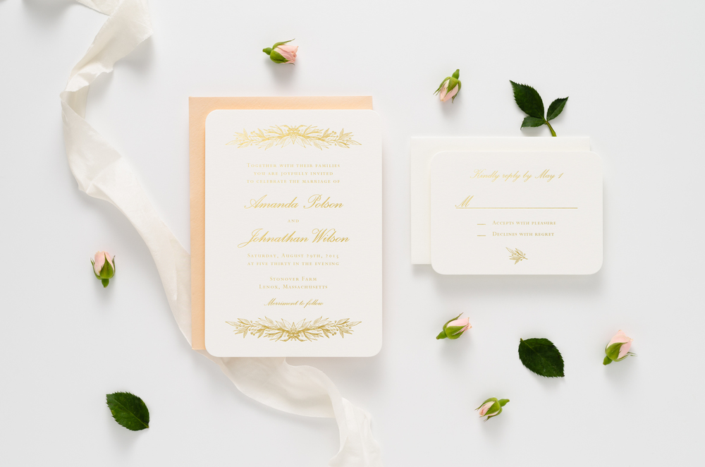 Elegant gold foil wedding invitation suite with decorative botanical accents