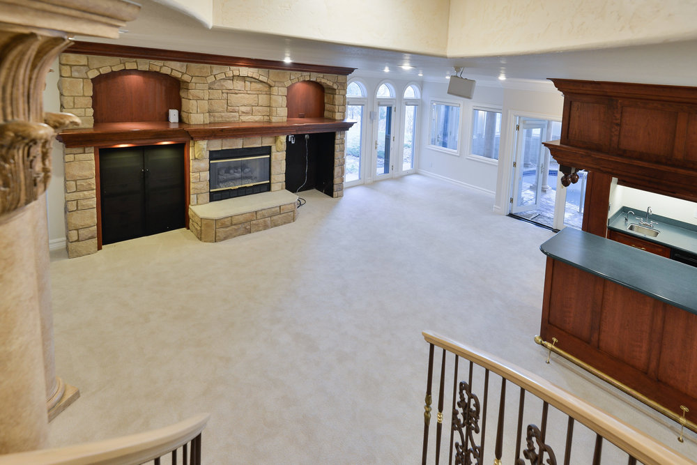 20 - Family room in lower level w fireplace, wet bar and game area.jpg