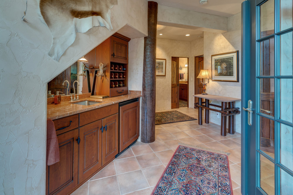 18-Hallway in lower level with wet bar with refrigerator on the left.jpg