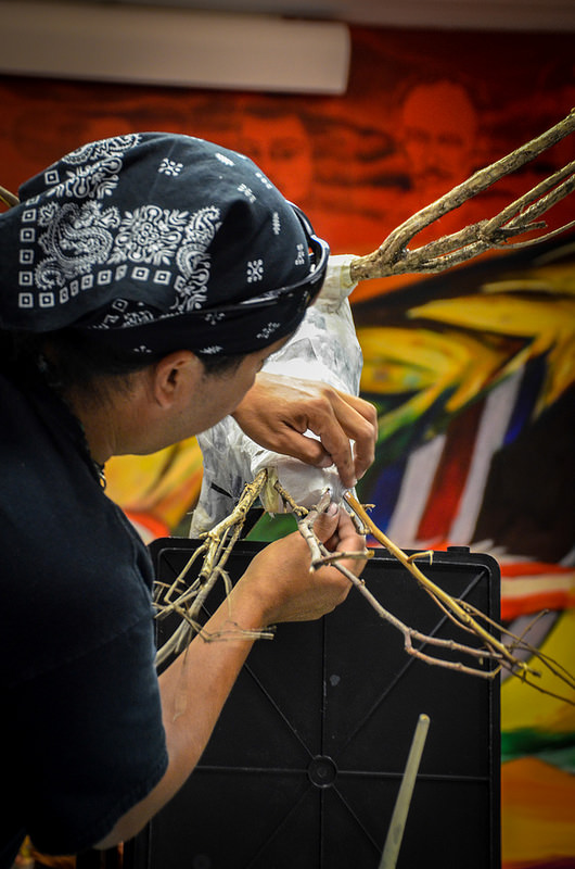 A person working on their bird sculpture