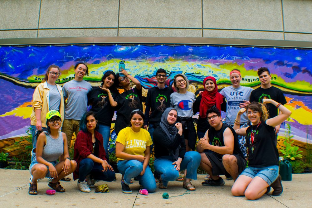 Student inters and leaders stand in front of the mural on the north side of the Latino Cultural Center.