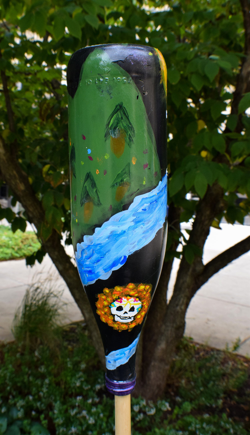 Erick's bottle featuring the river, nature scape, and a day of the dead skull