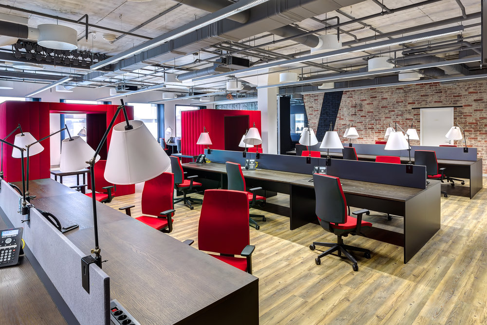interior of an office with bold red chairs and accent wall