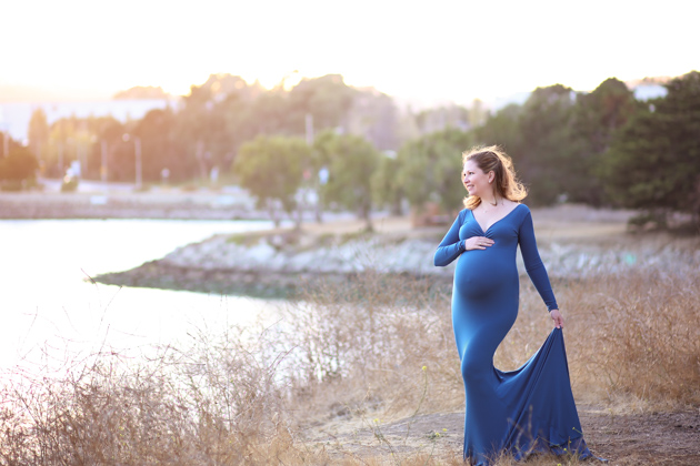 pregnant woman holding in maternity dress looking at sunset