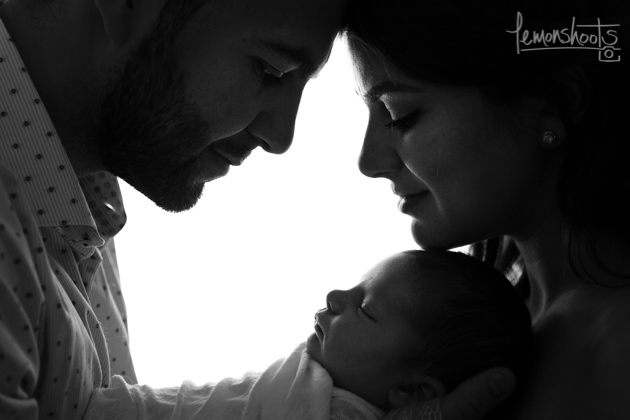 Parents with newborn baby, making a frame with their heads