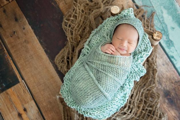 Alameda Newborn Photography Baby sleeping on tiny bed on wooden floor