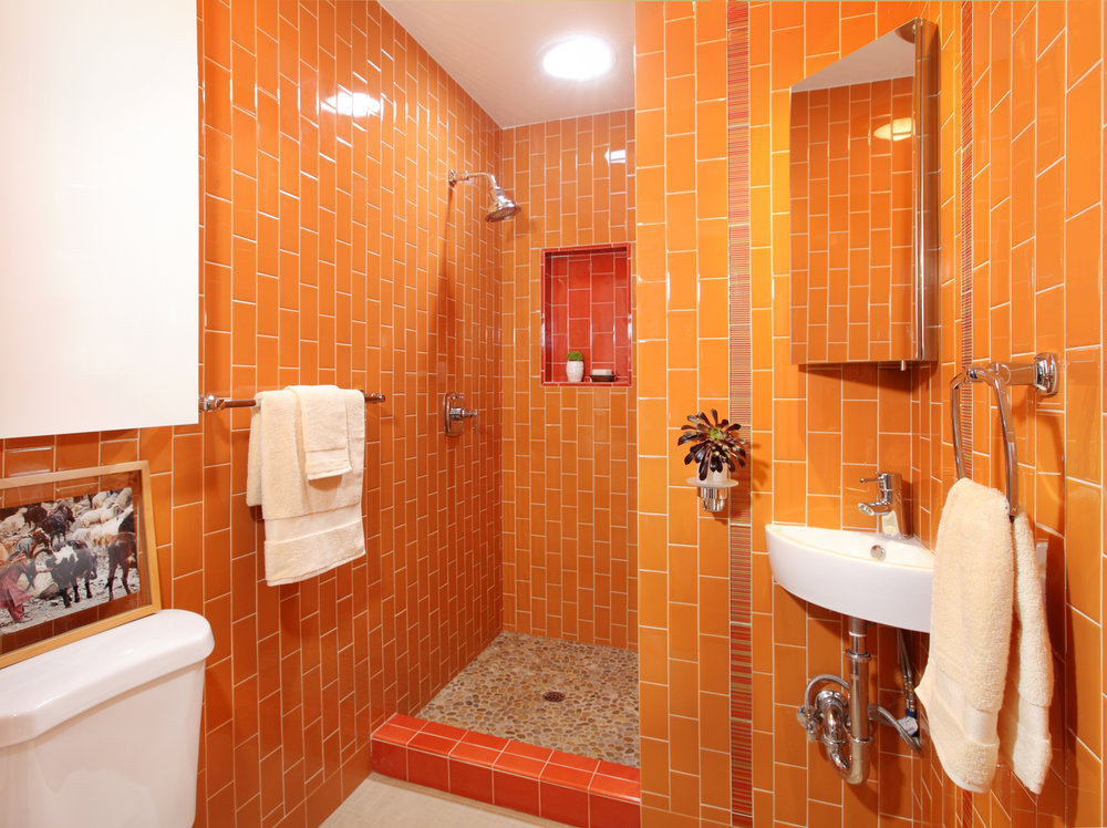 It's easy to feel energized in this West Hollywood bungalow bathroom covered head-to-toe in orange tiles. This cheerful and vibrant secondary color combines the energy of red and the happiness of yellow.