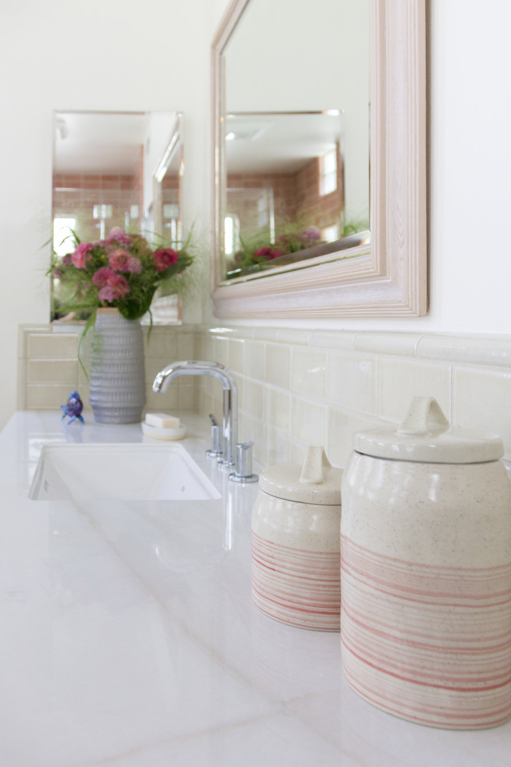 Cream and coral ceramic jars are a perfect storage solution for bathroom necessities.