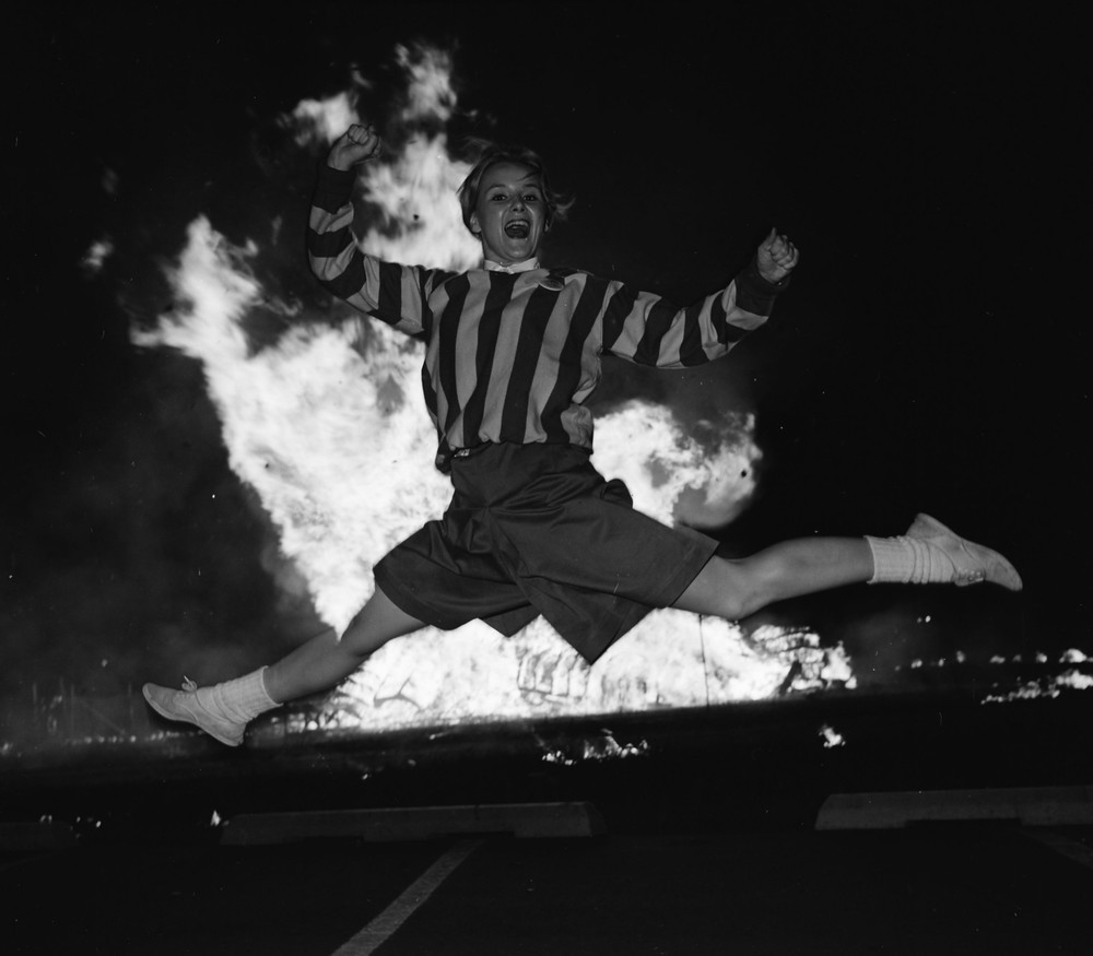 A bonfire the Friday night before the Homecoming Game was a tradition for many years.  Here we see a cheerleader jumping in front of the 1963 bonfire.