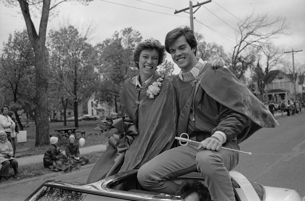 Enjoying the 1980 Homecoming Parade in style, King Pete Hein and Queen Mary Valentyn sit perched atop a car observing the crowd.