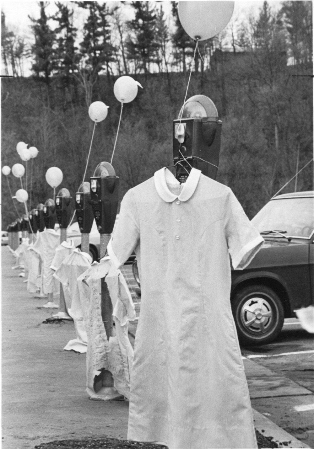 Nursing uniforms hanging on parking meters