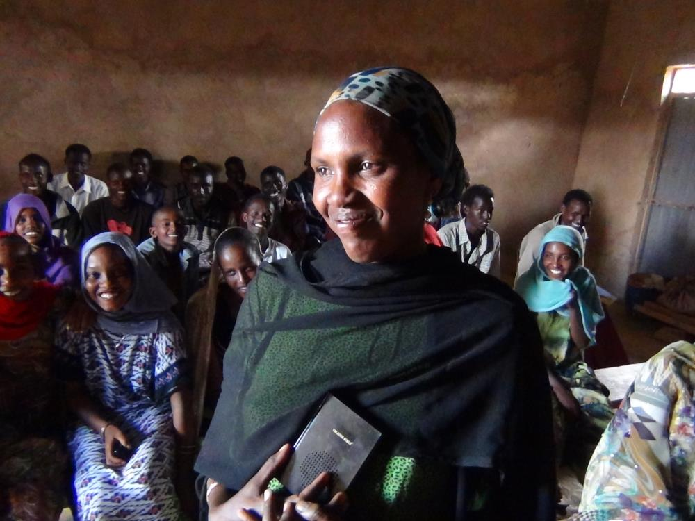 A refugee woman and her congregation beam while receiving their Talking Bibles.
