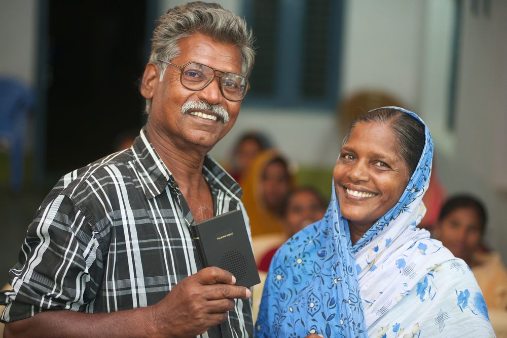 Yesuran and Rakshana stand with their Talking Bible in front of their church congregation.
