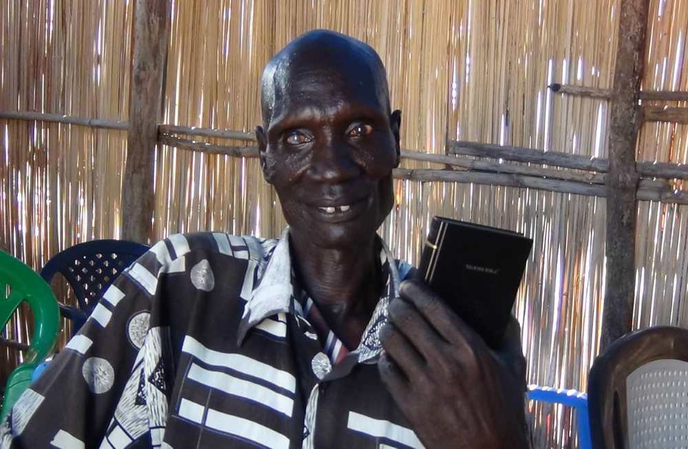 Babur smiles and holds his Talking Bible while sitting in the refugee church where we met him.