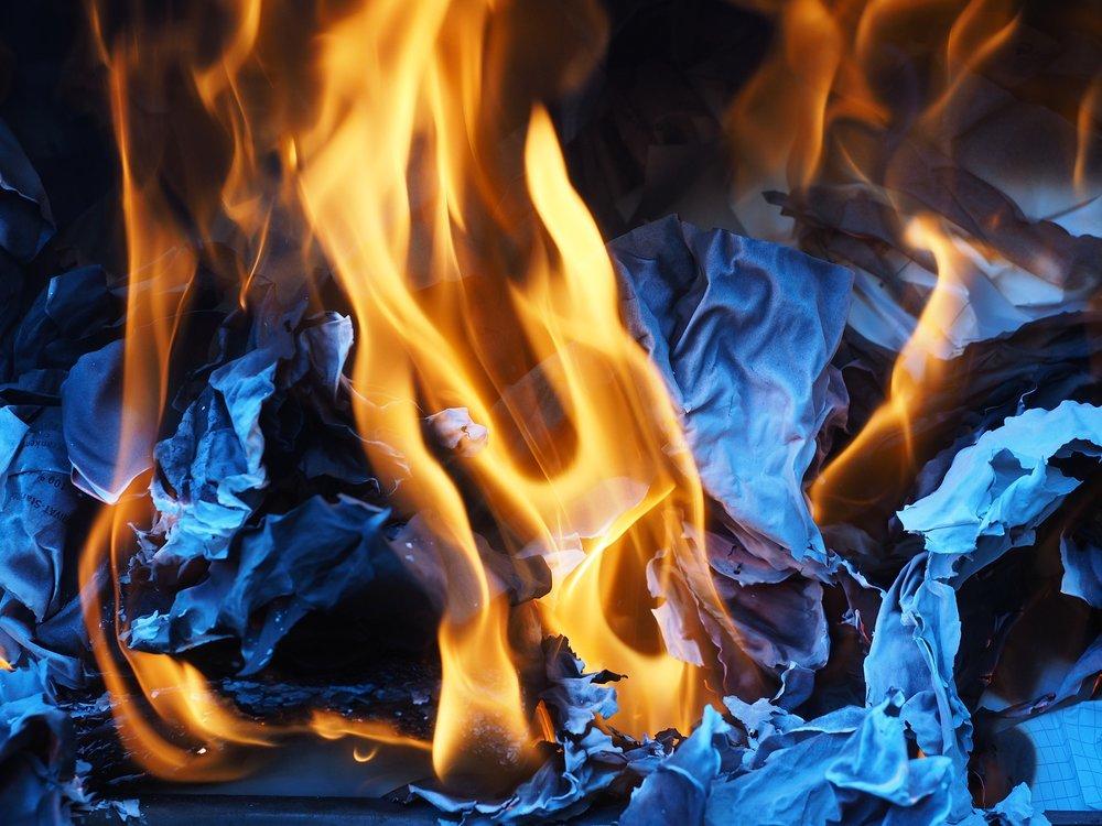 Unas llamas consumiendo unas hojas de papel.